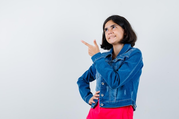 Молодая девушка держит руку на талии, смотрит в сторону, указывая влево в красной футболке и джинсовой куртке и выглядит задумчиво. передний план.