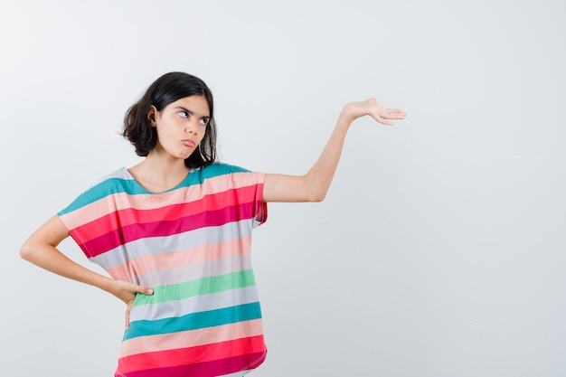 カラフルなストライプのtシャツで何かを持ってイライラしているように手を伸ばしながら腰に手をつないでいる少女。正面図。
