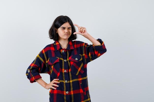 想像上の何かを持ってチェックシャツでウインクしてかわいく見えるように手を伸ばしながら腰に手をつないでいる少女。正面図。