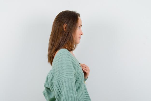 어린 소녀 니트에 가슴 위에 손을 잡고 매력적인, 전면보기를 찾고.
