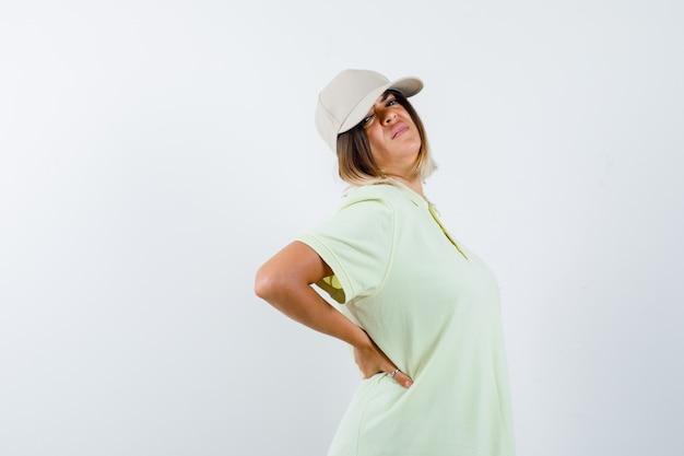 어린 소녀 t- 셔츠와 모자에 허리 뒤에 손을 잡고 지쳐 찾고. 전면보기.