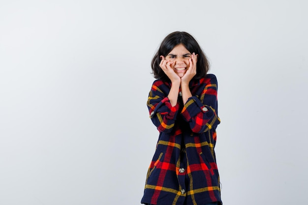 Young girl holding hands on cheeks in checked shirt and looking happy , front view.