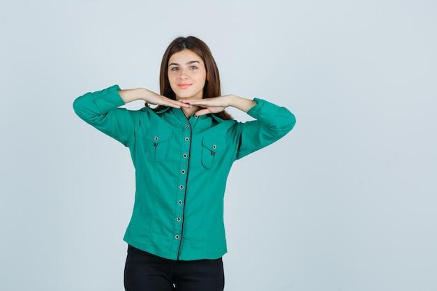Ragazza che tiene le mani sotto il mento in camicetta verde, pantaloni neri e sembra allegra. vista frontale.