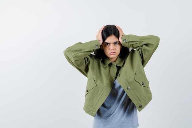 Young girl holding hands on head in grey sweater, khaki jacket, jean pant and looking serious , front view.