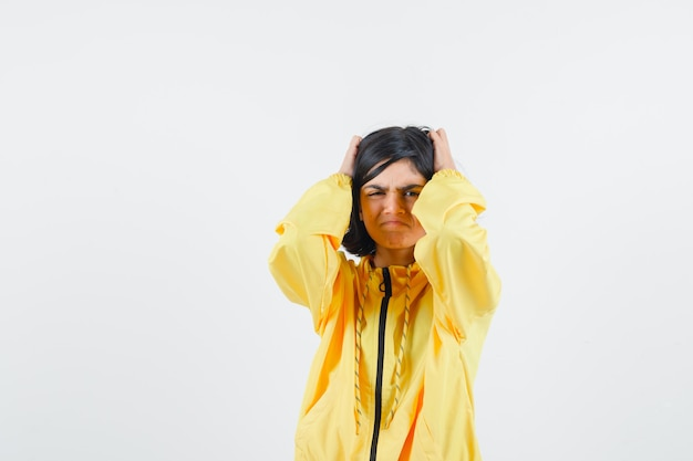 Young girl holding hands on head, having headache in yellow bomber jacket and looking harried.