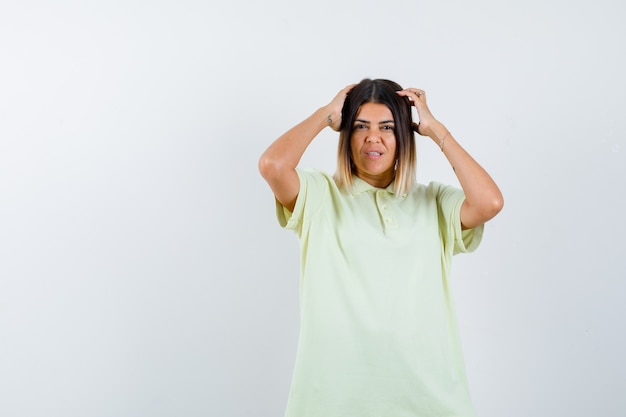 Young girl holding hands on head in t-shirt and looking uncomfortable , front view. Free Photo