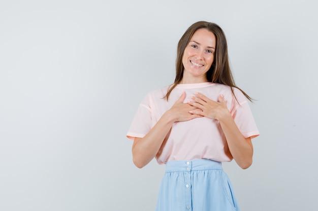 Ragazza che tiene le mani sul cuore in t-shirt, gonna e che sembra allegra. vista frontale.