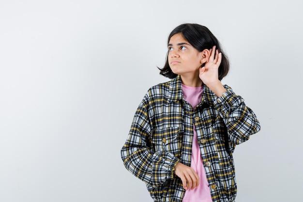 체크 셔츠와 분홍색 티셔츠를 입은 무언가를 듣기 위해 귀 근처에 손을 잡고 초점을 맞춘 앞모습을 바라보는 어린 소녀.