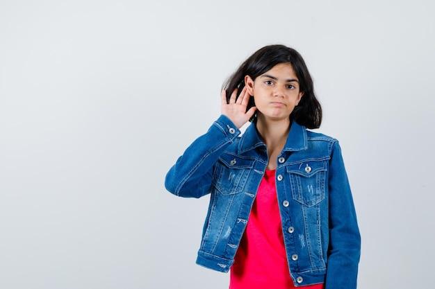 빨간 티셔츠와 진 재킷을 입은 무언가를 듣기 위해 귀 근처에 손을 잡고 초점을 맞추고 정면을 바라보는 어린 소녀.