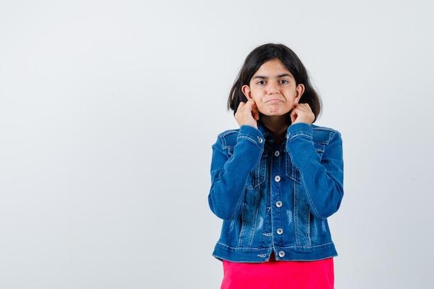 Молодая девушка держится за руки возле уха, чтобы услышать что-то в красной футболке и джинсовой куртке и смотрит сосредоточенно, вид спереди.