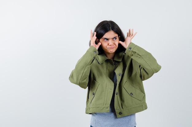 顔の近くで手をつないで、灰色のセーター、カーキ色のジャケット、ジーンズのパンツで目をそらし、物思いにふける少女。正面図。