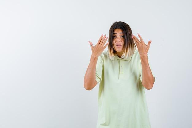 Tシャツを着て頭の近くで手を握って興奮している若い女の子、正面図。