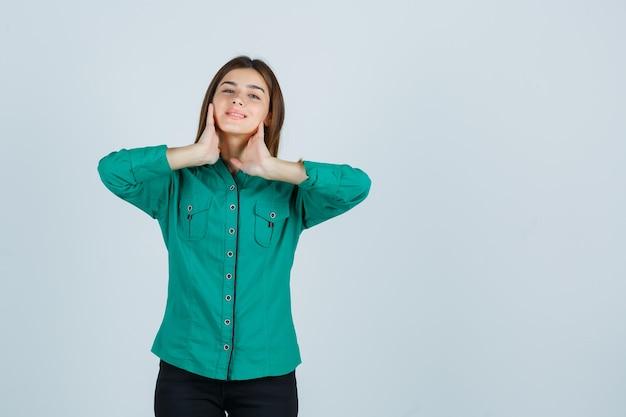 Ragazza che tiene le mani sul collo in camicetta verde, pantaloni neri e sembra carina. vista frontale.