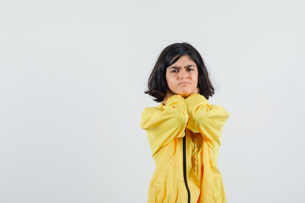 Ragazza che tiene le mani sul collo in giacca bomber gialla e che sembra seria