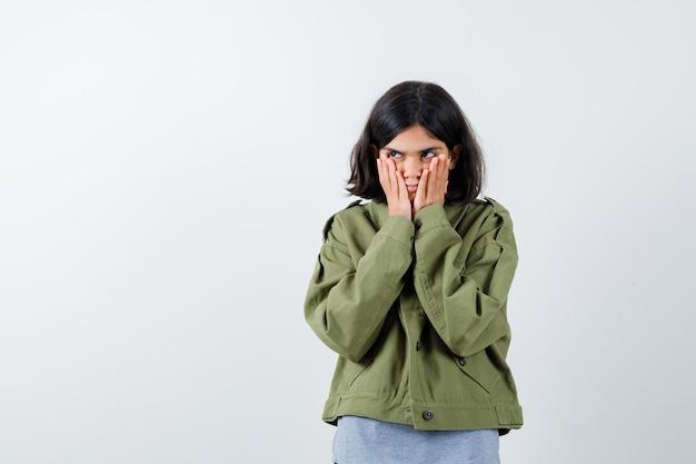 頬に手をつないで、灰色のセーター、カーキ色のジャケット、ジーンズのパンツで目をそらし、きれいに見える若い女の子。正面図。