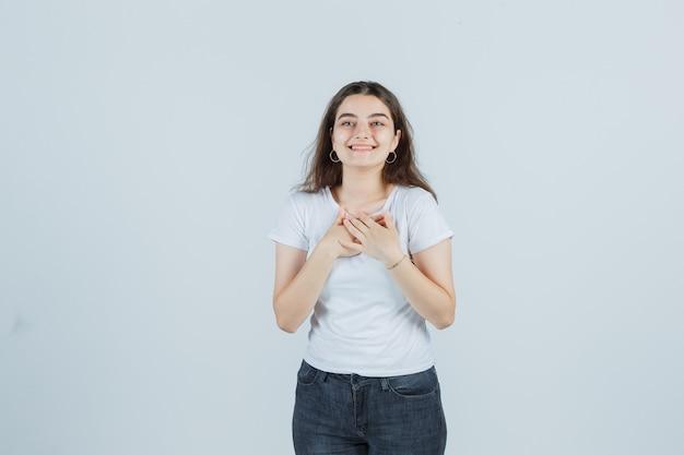 Молодая девушка держит руки на груди в футболке, джинсах и выглядит счастливой. передний план.