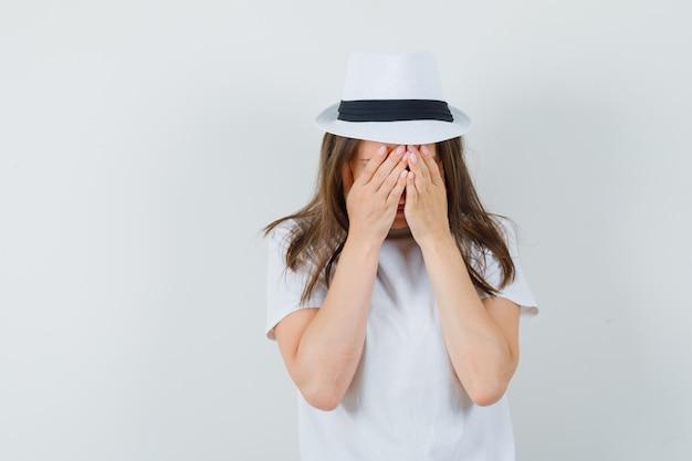 어린 소녀 흰색 t- 셔츠, 모자에 얼굴에 손을 잡고 우울, 전면보기를 찾고.