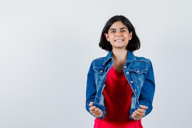赤いtシャツとジージャンのジャケットに手をつないで元気に見える少女。正面図。