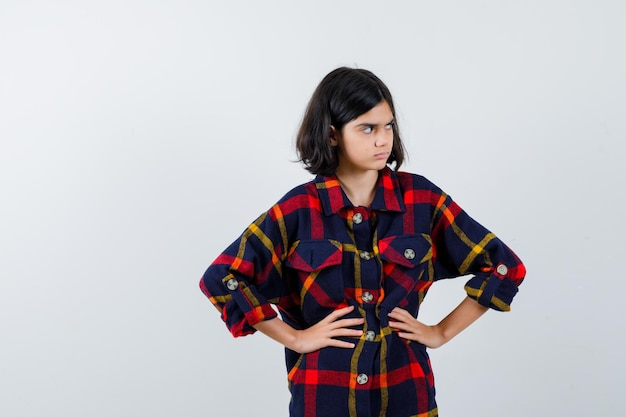 腰に手をつないで、チェックのシャツで目をそらし、自信を持って、正面図を見て若い女の子。