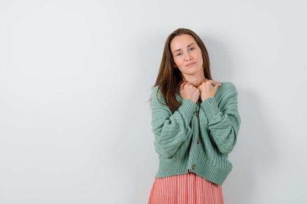 ニットウェア、スカートで胸に手をかざし、魅力的に見える少女。正面図。