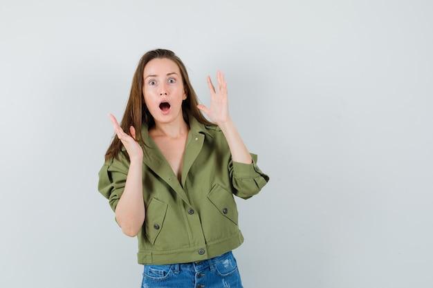 ジャケット、ショートパンツで手を上げて、驚いたように見える少女、正面図。
