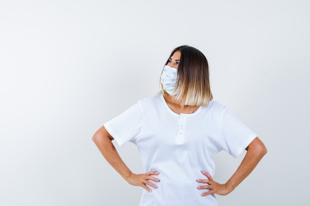 Young girl holding hands on waist, looking away in white t-shirt and mask and looking focused. front view.
