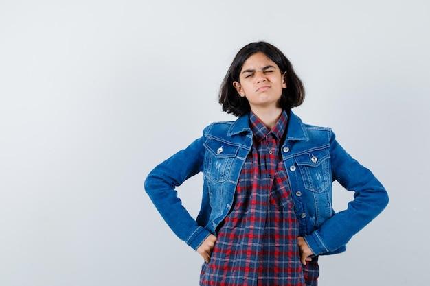 Giovane ragazza che si tiene per mano sulla vita, strizza l'occhio in camicia a quadri e giacca di jeans e sembra carina, vista frontale.