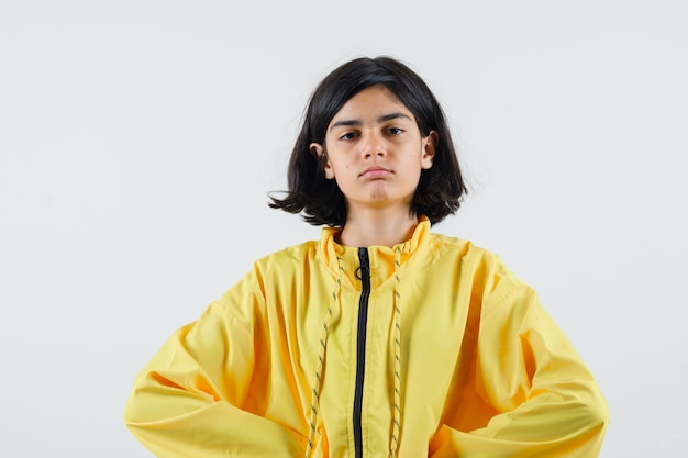 Young girl holding hands on waist in yellow bomber jacket and looking serious