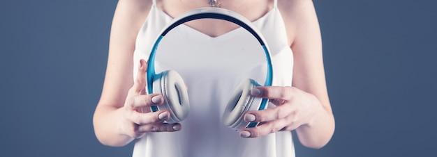 그녀의 손에 헤드폰을 들고 어린 소녀 프리미엄 사진