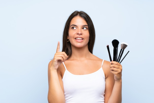 Young girl holding a lot of makeup brush intending to realizes the solution while lifting a finger up
