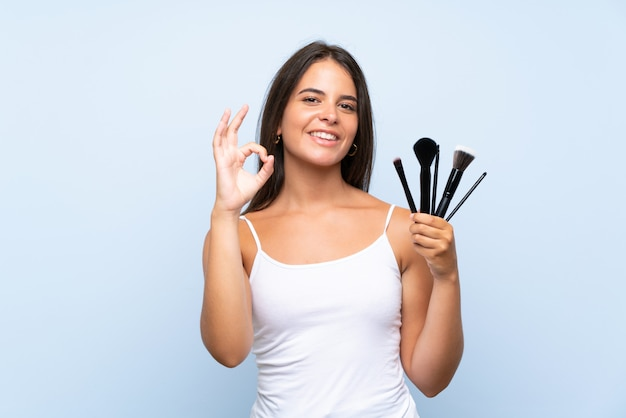 Young girl holding a lot of makeup brush showing ok sign with fingers