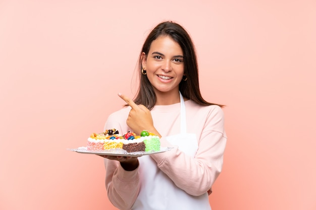 Young girl holding lots of different mini cakes over isolated wall pointing to the side to present a product