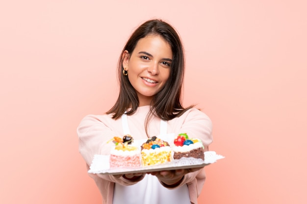 Young girl holding lots of different mini cakes over isolated wall