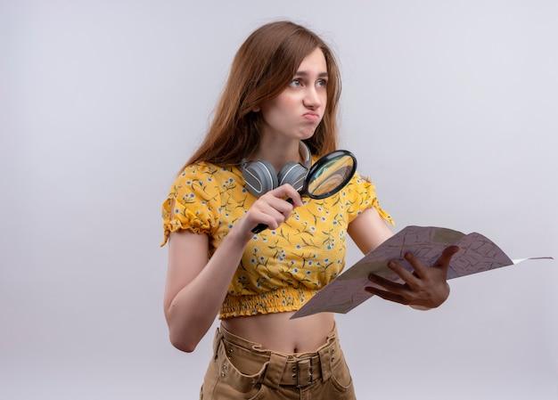 Ragazza giovane con lente di ingrandimento in vetro e mappa sulla parete bianca isolata con lo spazio della copia