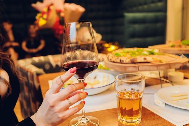 バーで赤い飲み物とマティーニグラスを保持している少女。