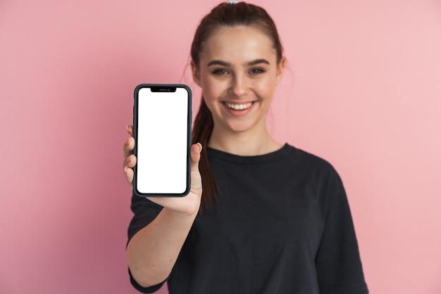 Молодая девушка держит мобильный телефон, показывая его экран
