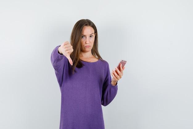 Ragazza che tiene il telefono cellulare con il pollice verso il basso in camicia viola e sembra deluso. vista frontale.