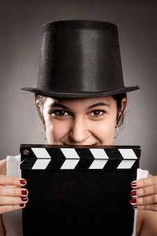 Young girl holding a movie clapper board