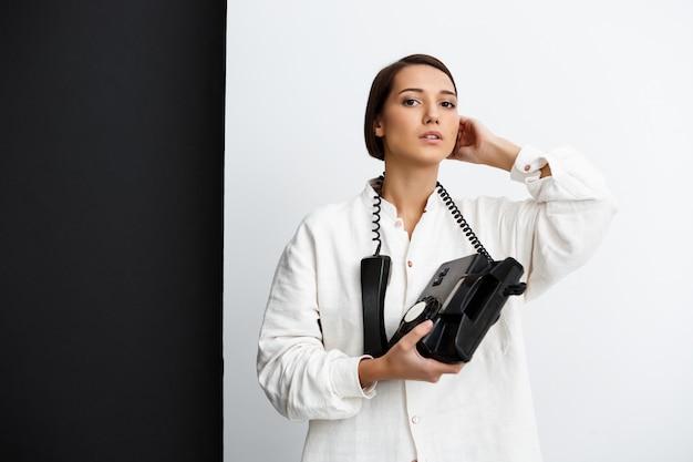 Молодая девушка держит старый телефон над черно-белой стеной