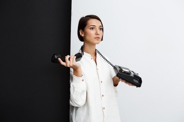 검은 색과 흰색 벽에 오래 된 전화를 들고 어린 소녀
