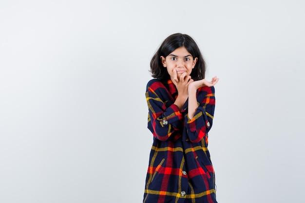 Giovane ragazza che tiene una mano sul mento mentre allunga la mano mentre tiene qualcosa di immaginario in una camicia a quadri e sembra eccitata, vista frontale.