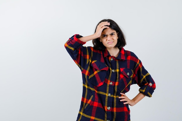 Young girl holding one hand on forehead, another hand on waist in checked shirt and looking angry , front view.