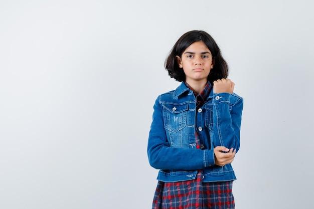 체크 셔츠와 진 재킷을 입고 한 손으로 팔을 잡고 진지한 정면을 바라보는 어린 소녀.