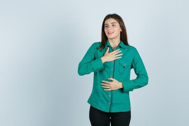 片方の手を胸に、もう片方の手を緑のブラウス、黒のズボンで腹に抱き、幸せそうに見える少女。正面図。