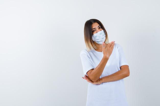 어린 소녀 팔꿈치 아래 한 손을 잡고 흰색 티셔츠와 마스크에 뭔가를 들고 심각한, 전면보기를 찾고 손을 스트레칭.