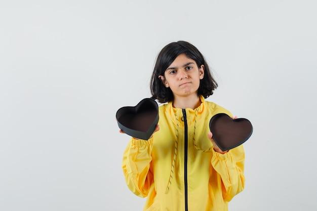 노란색 폭격기 재킷에 양손에 선물 상자를 열고 심각한 찾고 어린 소녀.
