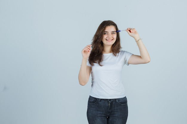 Young girl holding pen on head in t-shirt, jeans and looking joyful. front view.