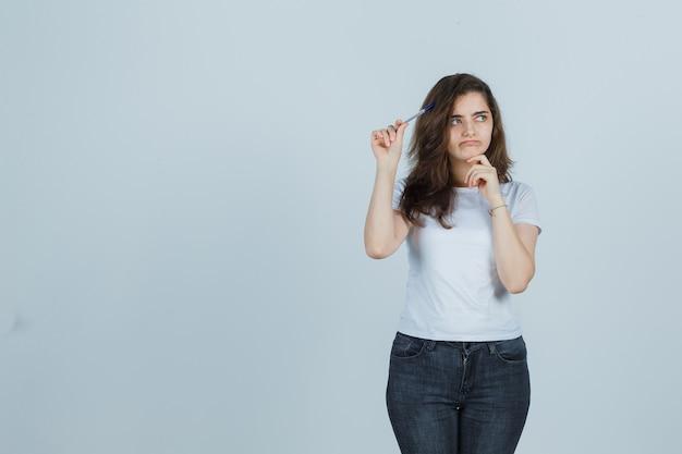 T- 셔츠, 청바지에 머리에 펜을 들고 사려 깊은 찾고 어린 소녀. 전면보기.