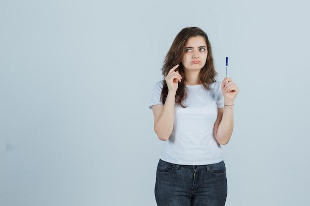 T- 셔츠, 청바지에 생각 하 고 사려 깊은 찾고있는 동안 펜을 들고 어린 소녀. 전면보기.