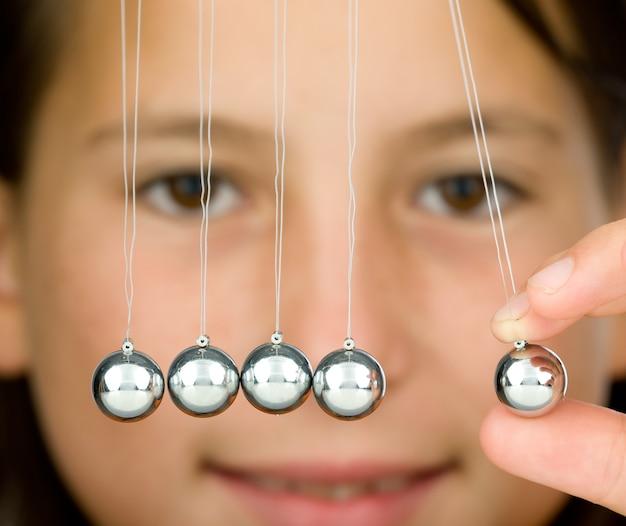 Young girl holding a pendulum ball